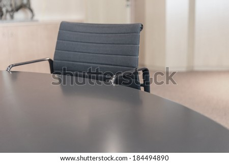 Table and armchair in a conference room - stock photo
