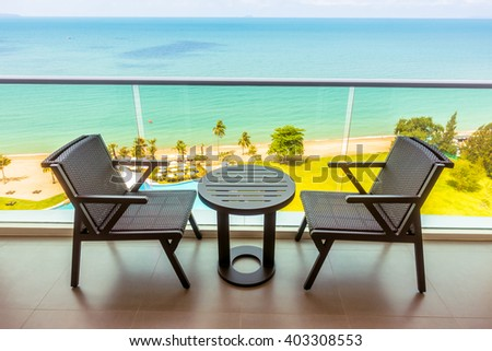 Table and chair with outdoor balcony and sea background - Vintage Filter and Boost up color Processing