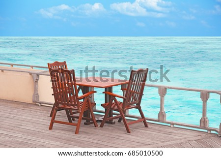 Table and chairs at sea beach on summer day