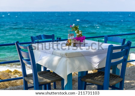 Table And Chairs In A Typical Tavern By The Sea At Rethymnon, Crete, Greece