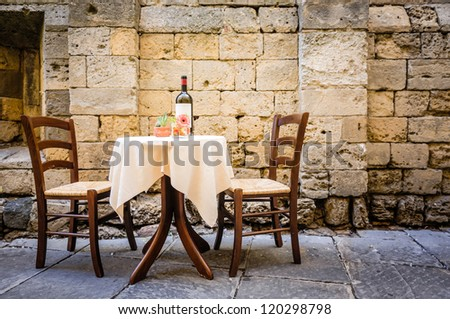 table and chairs in front of historic wall - tuscany/italy - stock photo