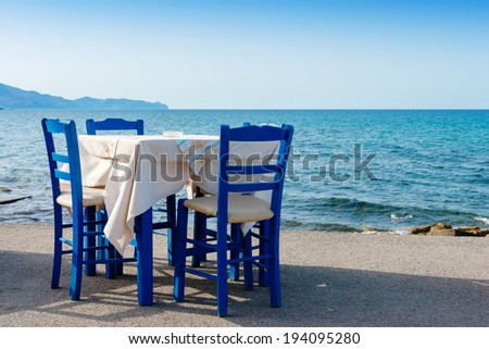 Table and chairs in sidewalk cafe at Kissamos, Crete, Greece  - stock photo
