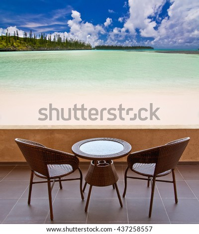 Table and chairs on a terrace, view on a tropical beach