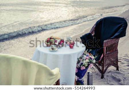 Table and chairs on seacoast for a romantic meeting