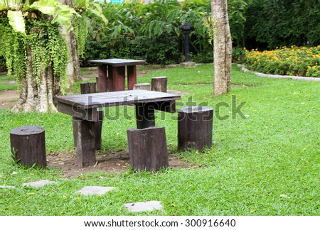 table and chairs standing on a lawn at the garden - stock photo