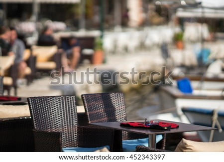 Table and cloth in the form of a ladybug on a blurred background of the city and port of Fiskardo at Kefalonia in Greece