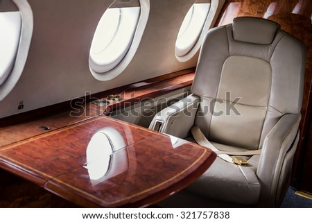 Table and seat inside of small business jet - stock photo
