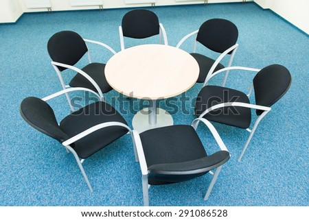 table and six chairs on the blue carpet - stock photo