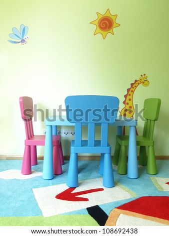 Table and three chairs in children's room - stock photo