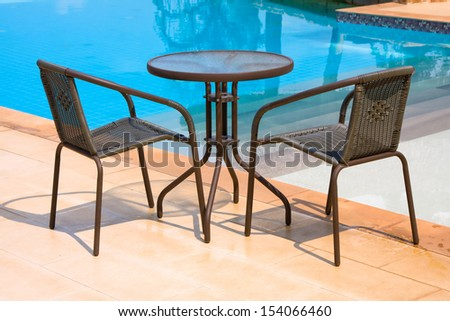 Table and two chairs next to the pool - stock photo