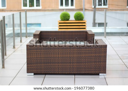 Table and wicker sofas in summer cafe on cinema terrace - stock photo