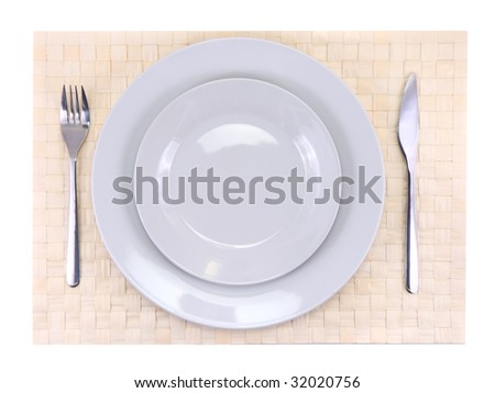 Table appointment-pile of plate,fork,spoon on beige wicker bamboo mat. All around Isolated.