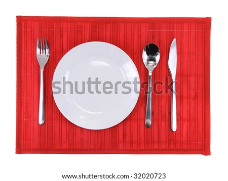Table appointment-plate,fork,knife, spoon on  red bamboo mat. All around Isolated.