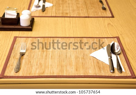Table appointments- fork,knife,spoon, silk napkin on  bamboo mat - stock photo