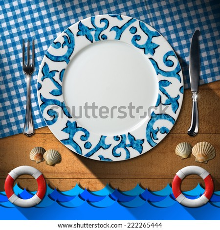 Table Arrangement for Seafood Menu / Empty plate with fork and knife, blue and white checkered tablecloth, seashells, blue waves and two lifebuoys. Table set for a seafood menu  - stock photo