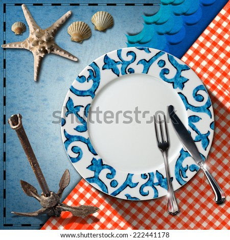 Table Arrangement for Seafood Menu / Empty plate with fork and knife, red and white checkered tablecloth, seashells, starfish, blue waves and rusty anchor. Table set for a seafood menu - stock photo