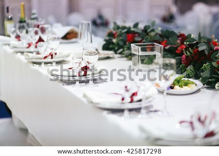 Table covered with white cloth served for a festive dinner