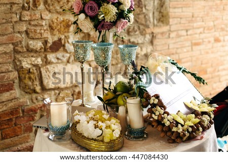 Table decor. High glasses pastel bouqet and white candles in blue pearls stand on the little round table - stock photo