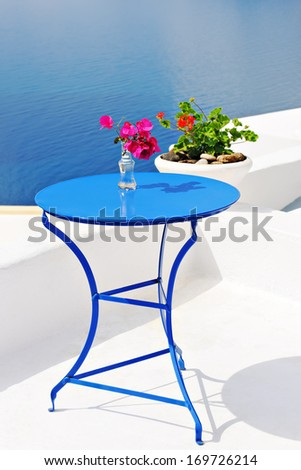 Table decorated with flowers on terrace overlooking sea in Oia, Santorini, Cyclades, Greece - stock photo