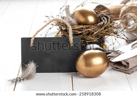 table decoration on white wooden background with chicken golden egg, with blackboard with space for text - stock photo