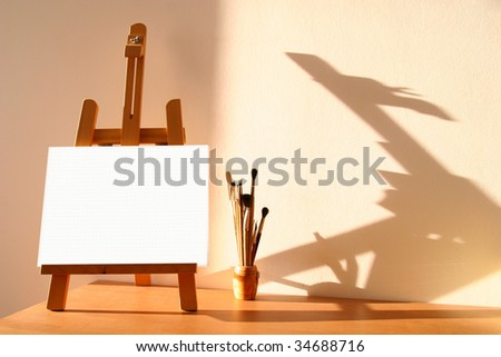 Table easel with canvas and brushes - stock photo