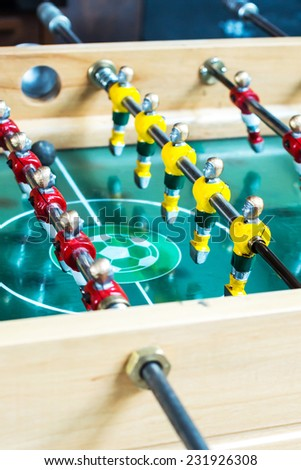 Table football game with yellow and red players - stock photo