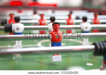 Table football table, football players and red rice wine. - stock photo