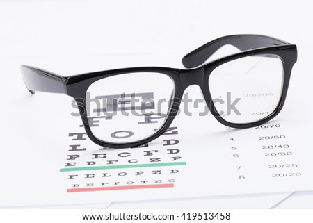 Table for eyesight test and glasses over it - studio shot - stock photo