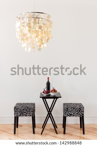 Table for two with bottle of red wine, in a room decorated with beautiful chandelier. - stock photo