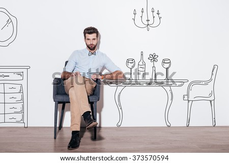 Table for two. Young handsome man keeping legs crossed and looking at camera while sitting in the chair against illustration of dining table in the background - stock photo