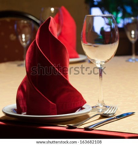 Table in a restaurant with a yellow tablecloth, red napkins, wine glasses and cutlery. - stock photo