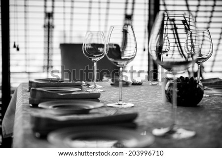 Table in restaurant served for lunch. Black and white abstract photo - stock photo