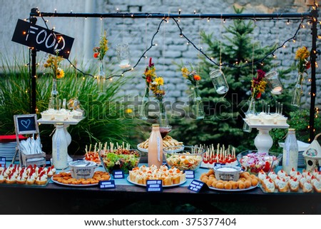 Table in the yard full of different finger food ready for the party.  - stock photo