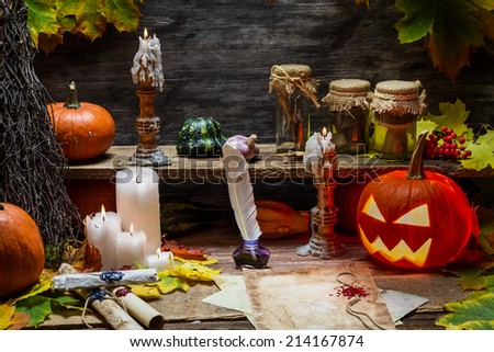 Table in witch hut with halloween pumpkin - stock photo