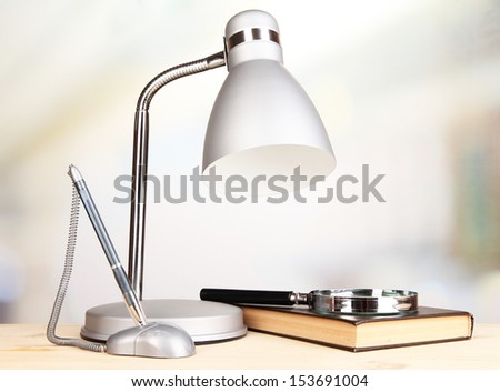 Table lamp and book on desk in room - stock photo