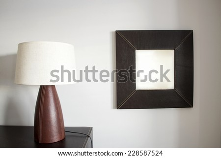 Table lamp and mirror in a bedroom - stock photo