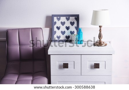Table lamp on commode in room - stock photo