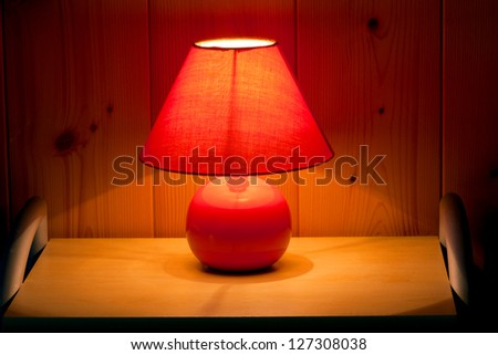 table lamp on wooden wall background - stock photo