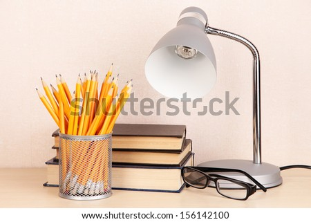 Table lamp with books on desk in room - stock photo