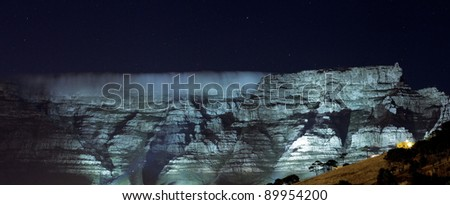 Table Mountain, Capetown, floodlit at night with stars and 'tablecloth' cover - stock photo