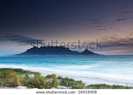 Table Mountain from Milnerton beach with grass in the foreground - stock photo