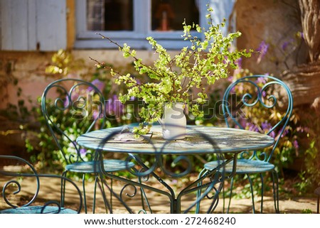 Table of cozy Parisian restaurant decorated with flowers - stock photo