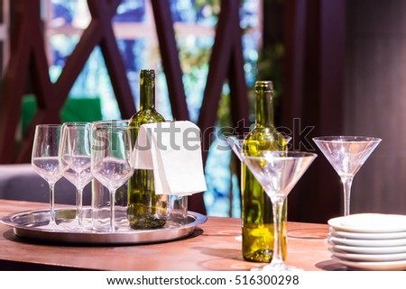 Table of empty glasses and bottle of wine