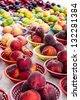 Table of fresh locally grown fruit in colorful baskets on display at farmers market - stock photo