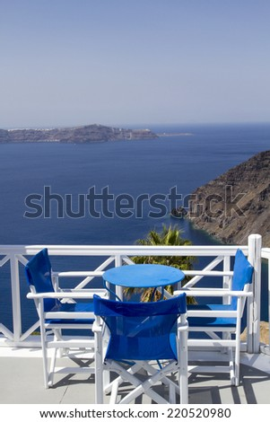 Table on terrace overlooking sea in Oia, Santorini, Cyclades, Greece - stock photo