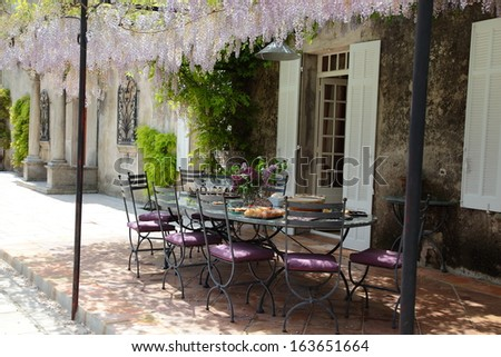 Table on the porch under blooming Wisteria - stock photo