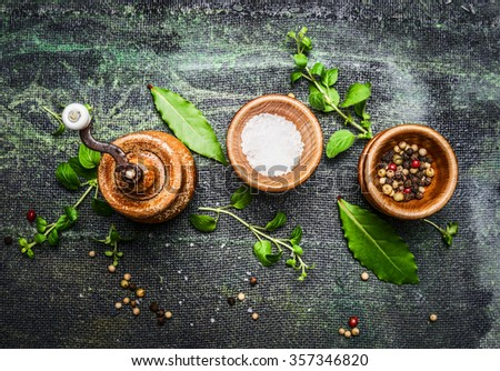 Table or cooking seasoning in wooden bowls on rustic background, top view - stock photo