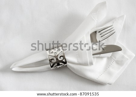 Table place setting with silver napkin ring, napkin and cutlery - stock photo