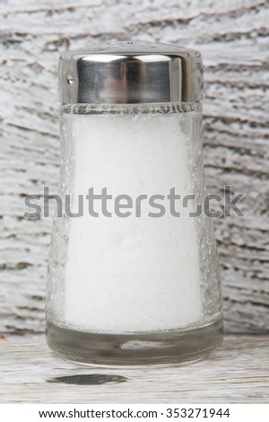 Table salt in glass condiment shaker over wooden background - stock photo