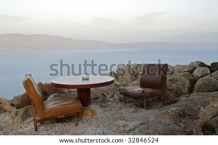 table & seats on the cliff - stock photo